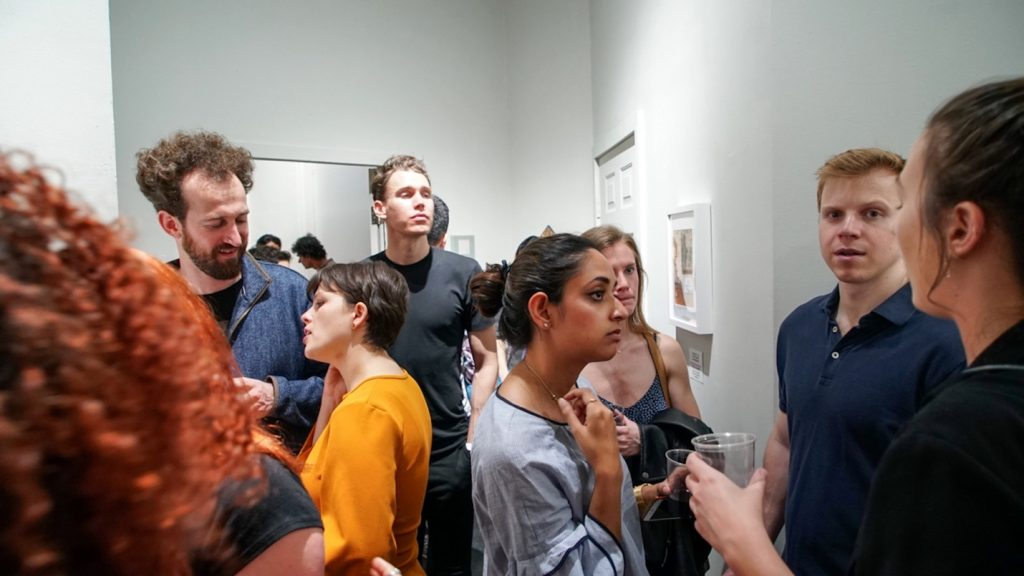 A group of people standing in a room Description automatically generated